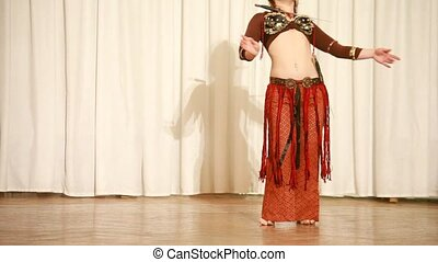 Female dancer in brown moves plastically with knifes
