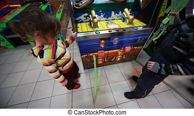 boy and girl wait while slot machine print lots of coupons -...