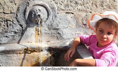 Little girl stands and drinks water from old source on wall