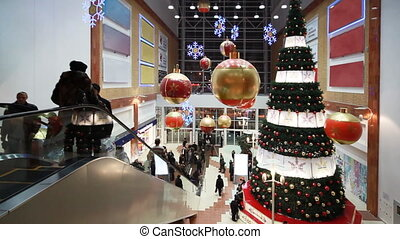 People move near big Christmas tree in shopping mall Golden...