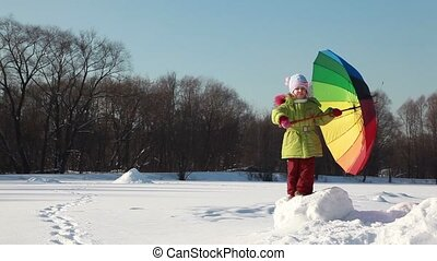 Girl stand on snow height and hold umbrella, she try to...