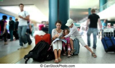 Mother and kids sit in airport and reading book