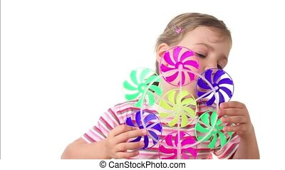 Girl holds fan set, she blows on blades, which are start to rotate