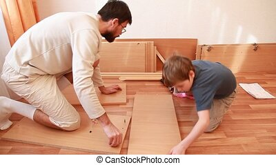 Father tightening screws in board and boy works with hammer sitting on floor
