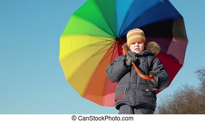 Boy stand and hold umbrella, he spins it by hook handle -...