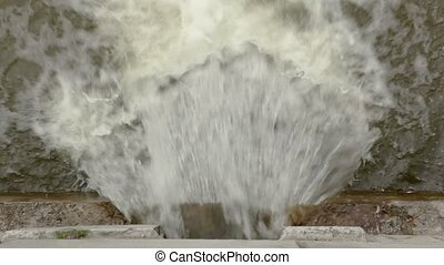 Water flow is pouring out of the hole in the stone wall