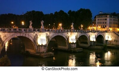 People walk along Sant Angelo Bridge at night, river flow...