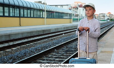 Boy with travel bag stands on train station near railway lines