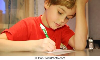 Close-up of boy very attentively writes something