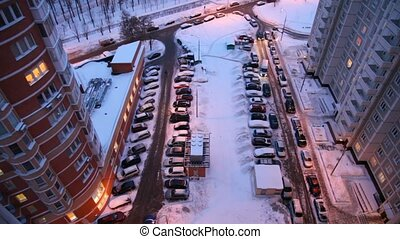 Top-down view on yard full of cars, winter evening