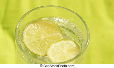 Glass of sparkling water and lemon refreshment background