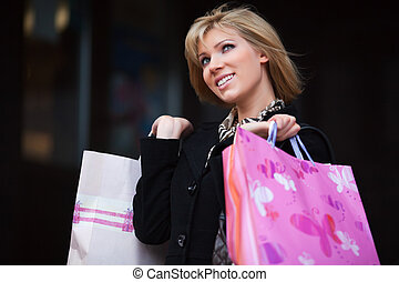 Happy shopper - Young woman with shopping bags on the steps