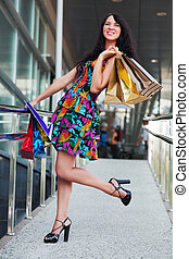 Happy shopper - Young woman with shopping bags against a...