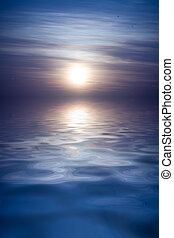 Moonrise - Full moon rises over large body of water, empty...