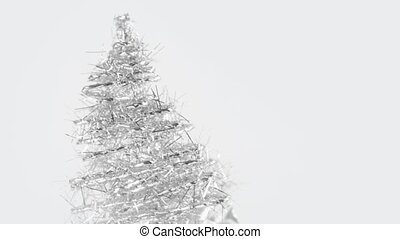 Close-up of rotating christmas tree made of tinsel grows...
