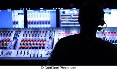 Silhouette of sound producer, which sits at mixer panel -...