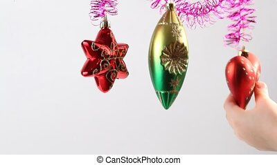 Christmas-tree decoration swing on tinsel, childrens hand...