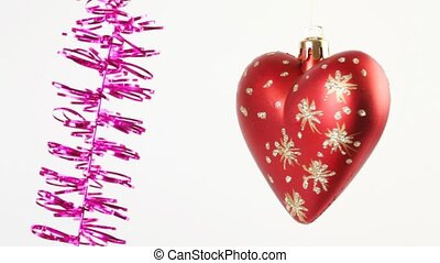 Christmas tree heart rotate near hanging tinsel