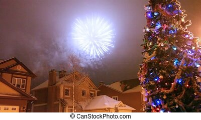 Salute in night sky over houses and christmas fir-tree