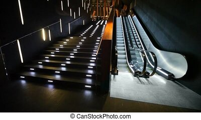 Escalator moves in empty hall, nearby is illuminated...