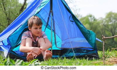 Boy with bare feet sits in tent at forest - Boy with bare...