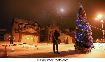 Firework in sky during a meeting of new year, in street there is high christmas fir-tree