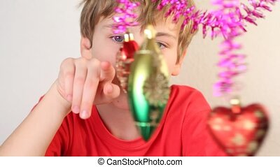 Boy play with christmas-tree decoration - Serious boy play...