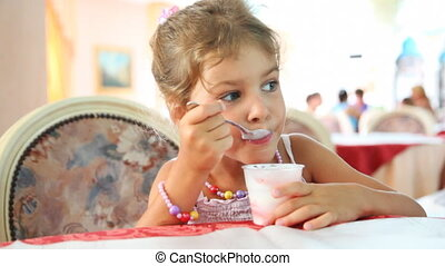 Little girl eats yogurt with spoon in plastic cup at table -...
