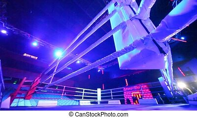 Empty ring geared-up for fight boxers in illuminated hall