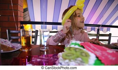 Little girl sits at table on the birthday, talk and eats pie...