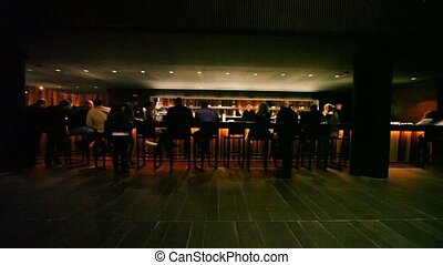 Many people sit at bar in big darkness hall of caf