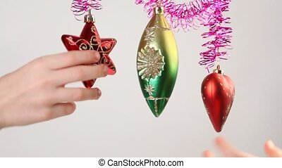 Childrens hands touches christmas-tree decoration, which...