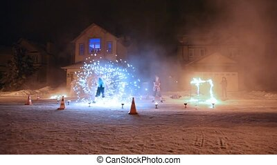 Fire show on winter street about houses at night