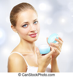 girl holding a box of cosmetic cream on a light background
