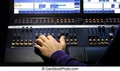 Hand of sound producer moving lie on mixer panel.