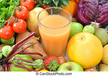 Fruit juice - Fruits and vegetables surrounding a glass of...