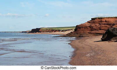 East coast beach. - Empty beach with red rocks and sand in...