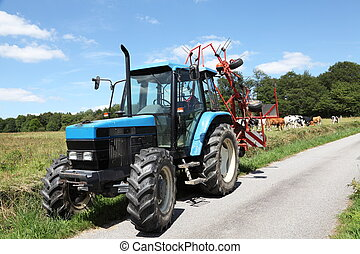 Summer Farm Road Tractor Hay Rake - A blue tractor with a...