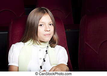 girl at the cinema - girl sitting alone in the cinema and...