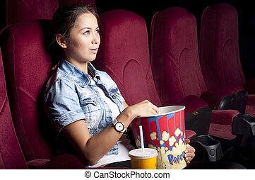 woman at the cinema eat popcorn - young woman sitting alone...