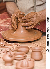 Working with raw clay. - Potter working with clay.