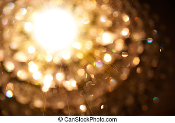 Golden particle of lights burst from the bright light