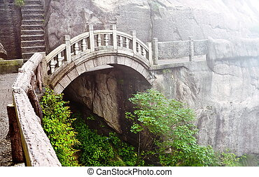 Stone bridge in Huangshan mountains - Foggy Stone bridge in...