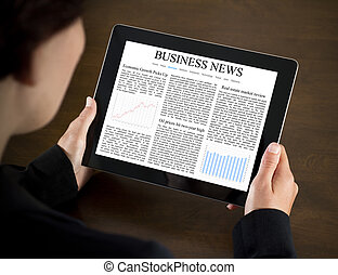 Reading Business News on Tablet PC - Business woman reading...