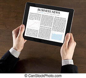 Business News On Tablet PC - Businessman hands are holding...