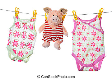 Baby sleepers and pig on the clothesline, studio isolated on...