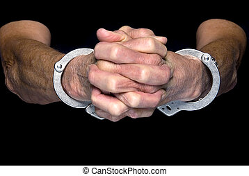 Handcuffed person - A person holds out their cuffed hands....