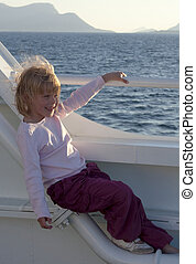 Girl on ferry boat, enjoying the view with wind in her hair