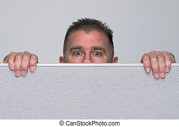 Man peering over office cubicle - A male office worker peers...