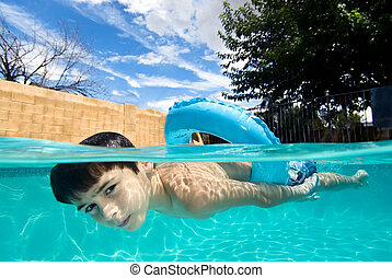Boy swimming in pool with float ring - A boy floats on his...